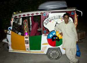 Adnan Khan standing in front of his Rickshaw Circus vehicle.