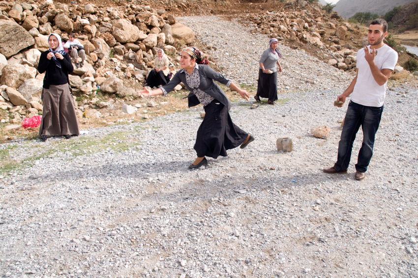 A Kurdish family plays a rock throwing game near the village of Bahcesaray