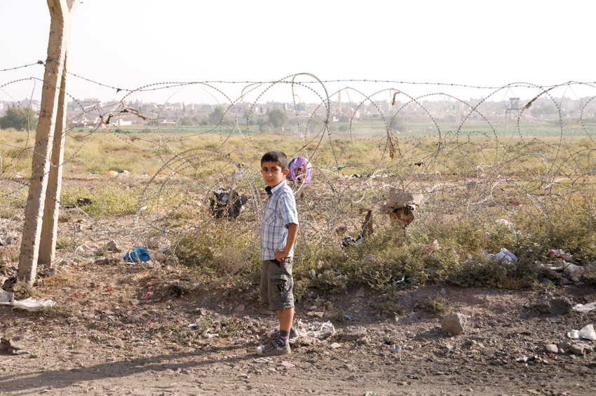 A Kurdish boy beside the Turkey-Syria border fence in the city of Nusaybin (with Qamishle in the background)