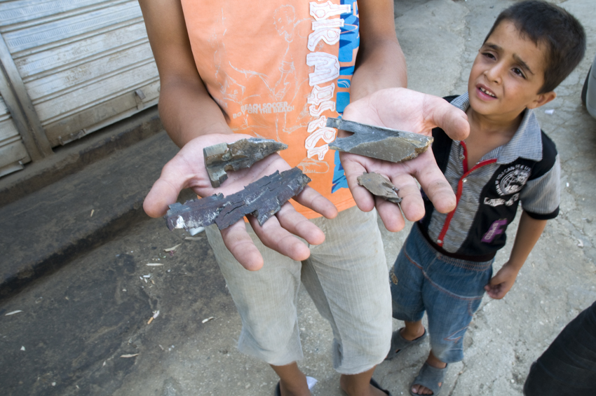 Syrian refugee children holding bomb shrapnel in the border village of Wadi Khaled, Lebanon