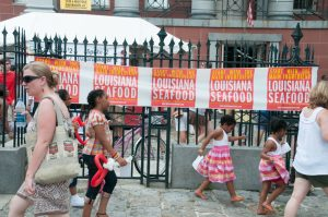 Residents in New Orleans pass by signs advertising the Louisiana seafood festival.